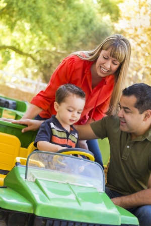 Happy Young Mixed Race Boy Enjoys A Toy Tractor While Parents Look On. photo