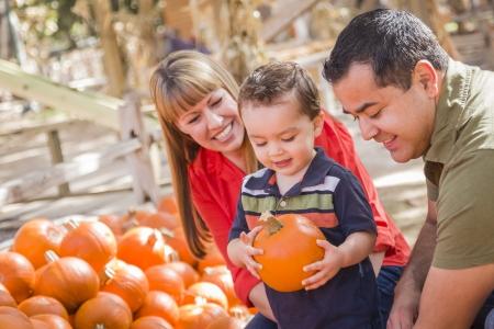 calabaza: Happy Family descendencia mixta Picking Pumpkins en el Pumpkin Patch.