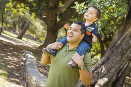 Happy Mixed Race Son Enjoys a Piggy Back Ride in the Park with Dad. photo