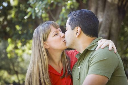 kiss couple: Happy Attractive Mixed Race Couple Enjoying A Day At The Park Together Stock Photo