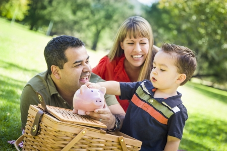 savings: Happy Mixed Race Couple Give Their Son a Piggy Bank at a Picnic in the Park.