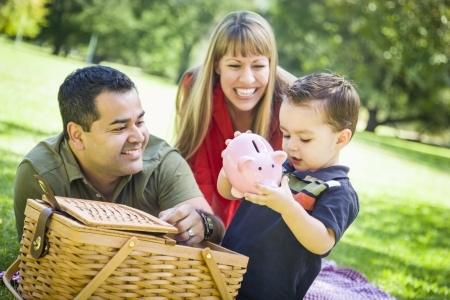 caucasian race: Happy Mixed Race Couple Give Their Son a Piggy Bank at a Picnic in the Park.