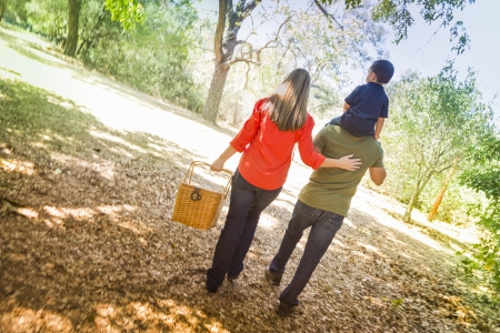 piggyback ride: Happy Mixed Race Family with Picnic Basket Enjoy a Walk in the Park. Stock Photo