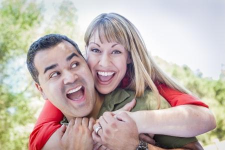 mixed race couple: Feliz Atractivo descendencia mixta Piggyback Pareja en el parque. Foto de archivo