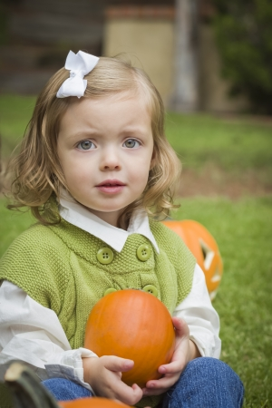 Adorable Young Child Girl Enjoying the Pumpkins at the Pumpkin Patch.