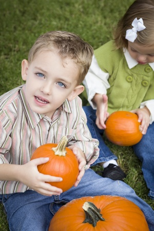 Cute Young Brother and Sister Children Enjoying the Pumpkins at the Pumpkin Patch. photo