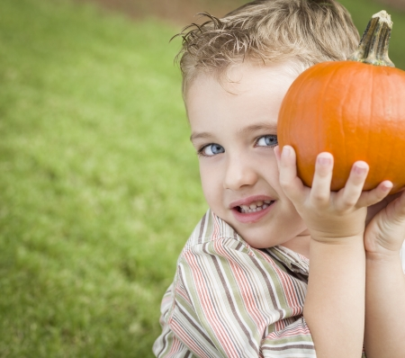 Adorable Young Child Boy Enjoying the Pumpkins at the Pumpkin Patch. photo