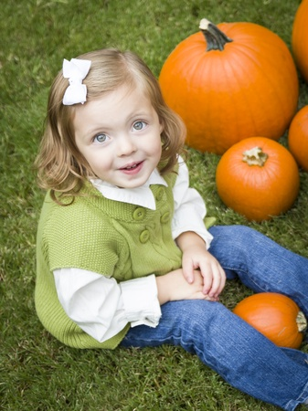 Adorable Young Child Girl Enjoying the Pumpkins at the Pumpkin Patch. photo