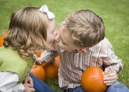 かわいい弟と妹子パンプキン パッチでカボチャの中でキスします。