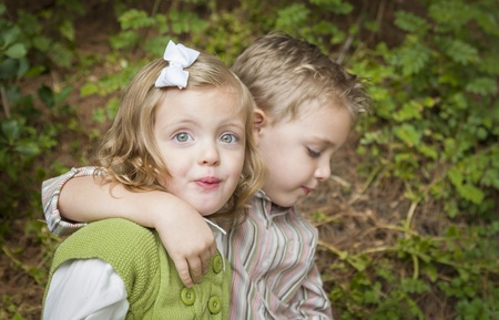 Adorable Brother and Sister Children Hugging Each Other Outside. photo
