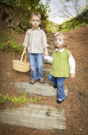 Adorable Brother and Sister Children Holding Hands Walking Down Wood Steps with Basket Outside. photo