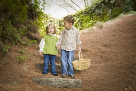 kids holding hands: Adorable Brother and Sister Children Holding Hands Walking Down Wood Steps with Basket Outside. Stock Photo