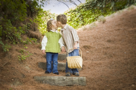Adorable Brother and Sister Children with Basket Kissing Outside. photo