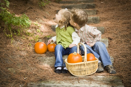Adorable Brother and Sister Children Sitting on Wood Steps with Pumpkins Whispering Secrets or Trying to Kiss Cheek. photo