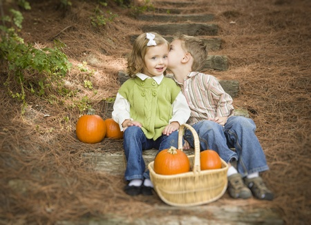 Adorable Brother and Sister Children Sitting on Wood Steps with Pumpkins Whispering Secrets or Kissing Cheek. photo