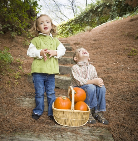 Adorable Brother and Sister Children Sitting on Wood Steps with Basket of Pumpkins Singing Songs Outside. photo