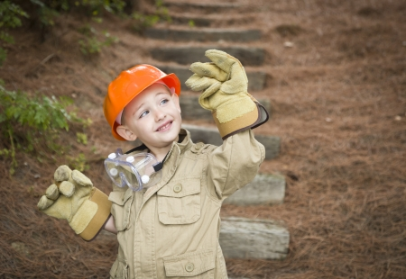Happy Adorable Child Boy with Big Gloves, Hard Hat and Goggles Playing Handyman Outside. photo