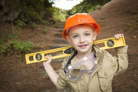 hard: Happy Adorable Child Boy with Level, Hard Hat and Goggles Playing Handyman Outside. Stock Photo