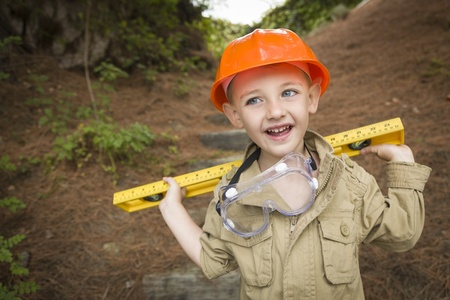 Happy Adorable Child Boy with Level, Hard Hat and Goggles Playing Handyman Outside. photo