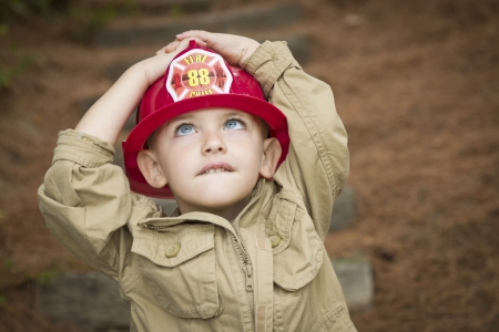 the fireman: Happy Adorable Child Boy with Fireman Hat Playing Outside.