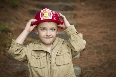 Happy Adorable Child Boy with Fireman Hat Playing Outside. photo