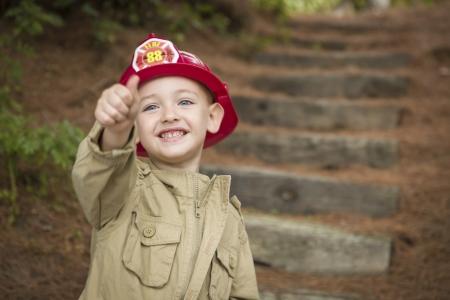 bombero de rojo: Niño feliz Niño adorable con el sombrero de bombero y Pulgares arriba jugando afuera. Foto de archivo
