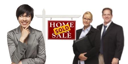 Gemengde Race Mensen met Verkocht Home For Sale Real Estate Sign Geïsoleerd op een witte achtergrond