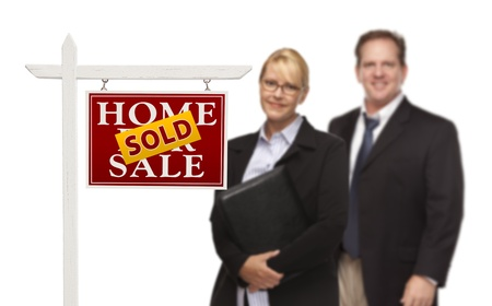 Businesswoman and Businessman Behind Sold Home For Sale Real Estate Sign Isolated on a White Background. Stock Photo - 15867517