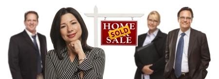 Mooie Spaanse Vrouw en andere mensen achter in Front van Verkocht Home Te Koop Real Estate Sign Geïsoleerd op een witte achtergrond.