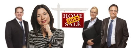 Pretty Hispanic Woman and Other People Behind in Front of Sold Home For Sale Real Estate Sign Isolated on a White Background.