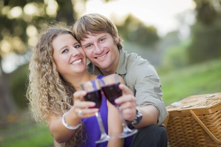 An Attractive Couple Enjoying A Glass Of Wine in the Park Together. photo