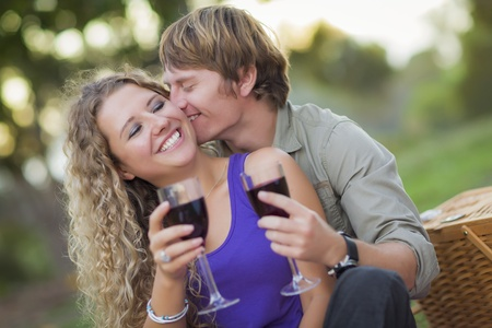 man woman hugging: An Attractive Couple Enjoying A Glass Of Wine in the Park Together.