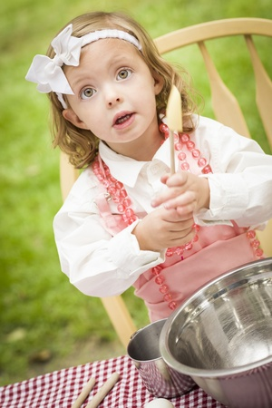 Happy Adorable Little Girl Playing Chef Cooking in Her Pink Outfit. Stock Photo