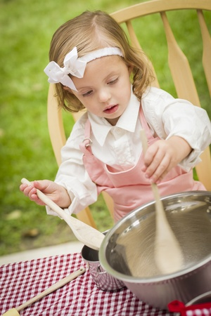 dressup: Happy Adorable Little Girl Playing Chef Cooking in Her Pink Outfit. Stock Photo
