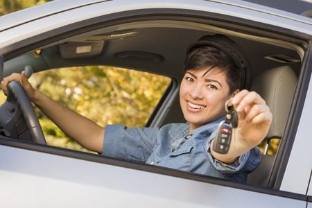 Gelukkige het Glimlachen Mixed Race vrouw in auto Holding set sleutels. Stockfoto