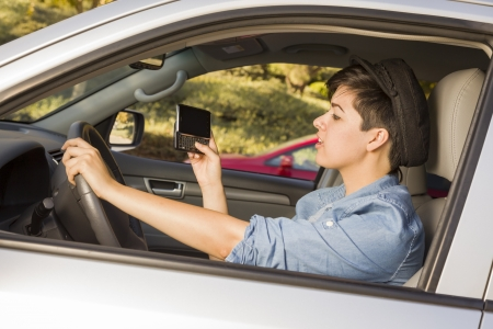 Mixed Race Woman with Smart Phone Texting and Driving. Imagens