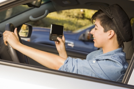 adult texting: Mixed Race Woman with Smart Phone Texting and Driving. Stock Photo
