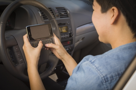 reckless: Mixed Race Woman with Smart Phone Texting and Driving. Stock Photo