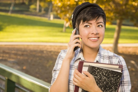 Outdoor Portrait of a Pretty Mixed Race Female Student Holding Books and Talking on Her Cell Phone on a Sunny Afternoon. photo