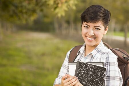 Outdoor Portrait of a Pretty Mixed Race Female Student Holding Books on a Sunny Afternoon. photo