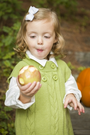 Adorable Child Gilr Eating a Delicious Red Apple Outside. photo