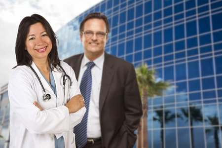 paediatrician: Doctor o enfermera hisp�nico atractivo y hombre de negocios delante del edificio corporativo. Foto de archivo