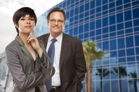 Attractive Mixed Race Woman and Businessman in Front of Corporate Building. photo
