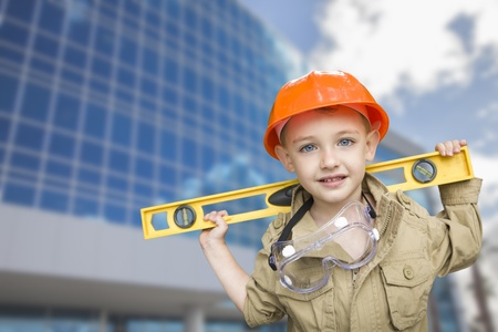 Adorable Child Boy Dressed Up as a Handyman in Front of Corporate Building. photo