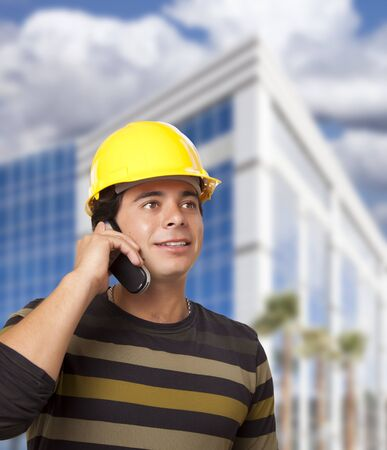 Handsome Hispanic Male Contractor on Cell Phone in Front of Corporate Building. photo