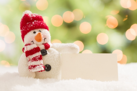 Cute Snowman with Scarf and Hat Next To Blank White Card Over Abstract Background photo