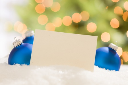 room for text: Blue Christmas Ornaments Behind Blank Off-white Card Ready for Your Own Text.  Stock Photo