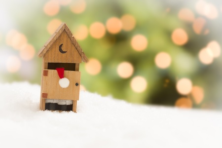 Santa in A Miniature Outhouse on Snow Over and Abstract Background. photo