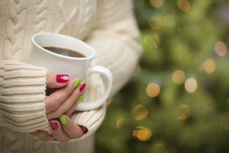 christmas morning: Woman in Sweater with Seasonal Red and Green Nail Polish Holding a Warm Cup of Coffee. Stock Photo