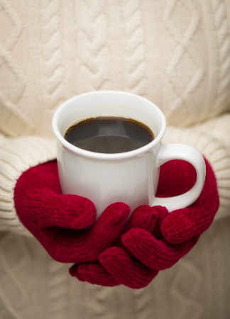 cold weather: Woman in Sweater with Seasonal Red Mittens Holding a Warm Cup of Coffee.